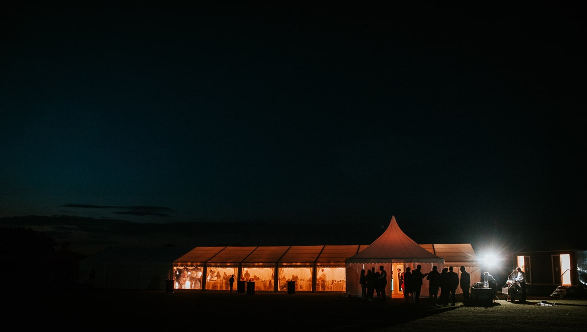 Night time exterior shot of a clear span marquee and a chinese hat marquee | County Marquees East Anglia